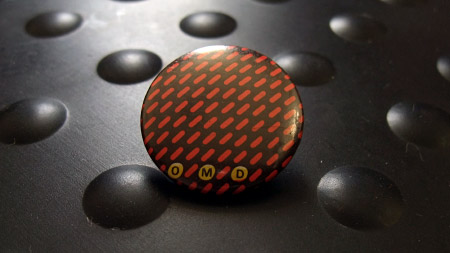 OMitD badge - first album 'lozenge' grid pattern in red again