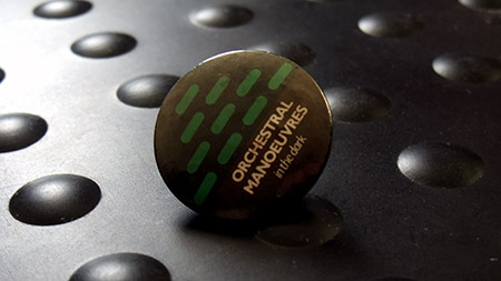 OMitD badge - first album 'lozenge' grid pattern in green
