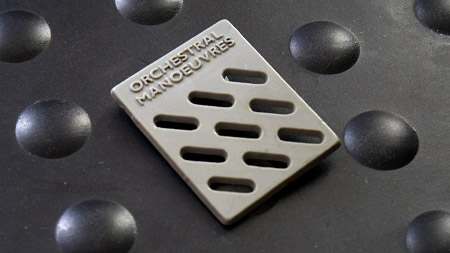 OMitD badge - first album 'lozenge' grid pattern in grey plastic