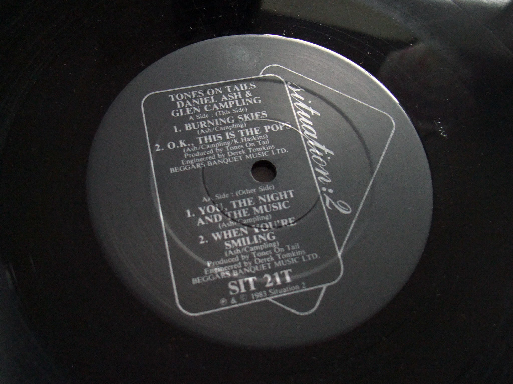 Tones On Tail - Burning Skies / OK This is The Pops 7 inch single side 1 label design